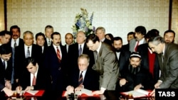Tajik President Emomali Rahmon (left) and opposition leader Said Abdullo Nuri (right) sign an agreement on national reconciliation in Moscow in December 1996.