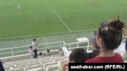 Bir aýal maşgala futbol duşuşygyna tomaşa edýär. Türkmenistanyň Futbol çempionaty. 2013 ý.