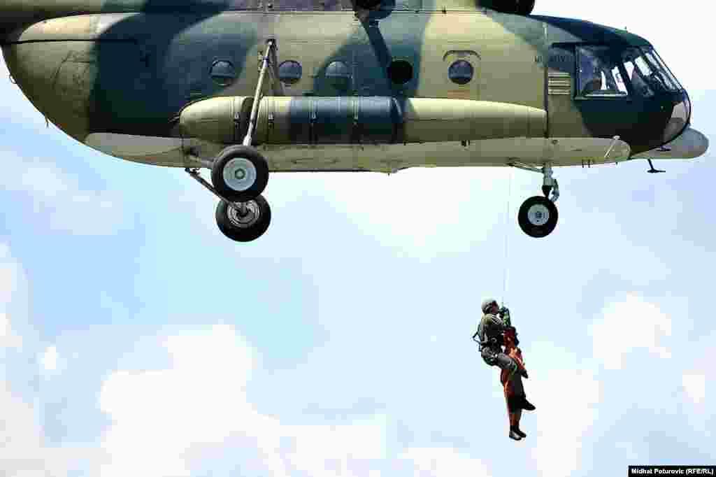 Helikopter Mi-8 MTV dolazi iznad osigurane površine i dizalicom podiže specijalistu STS-a i povrijeđenog.