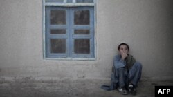 د افغانستان د مارجه ولسوالۍ د کور مخې ته ناست یو ماشوم