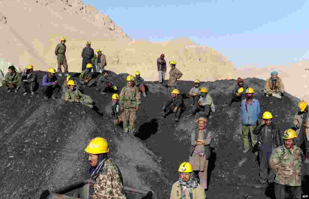 Miners wait on September 16 to remove the bodies of their colleagues who died in a mine collapse in the Ruyi Du Ab district of Samangan Province.