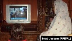 سيدة عراقية تتابع مسلسلا نلفزيونيا