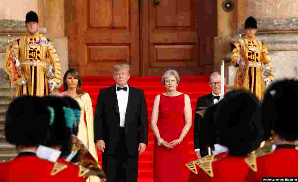 U.K. -- British Prime Minister Theresa May and her husband Philip stand together with U.S. President Donald Trump and first Lady Melania Trump at the entrance to Blenheim Palace, where they are attending a dinner with specially invited guests and business