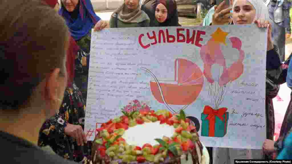Abdurahmanovnıñ qadınını qızınen beraber plakatlar ve üfürikler ile qarşılay ediler