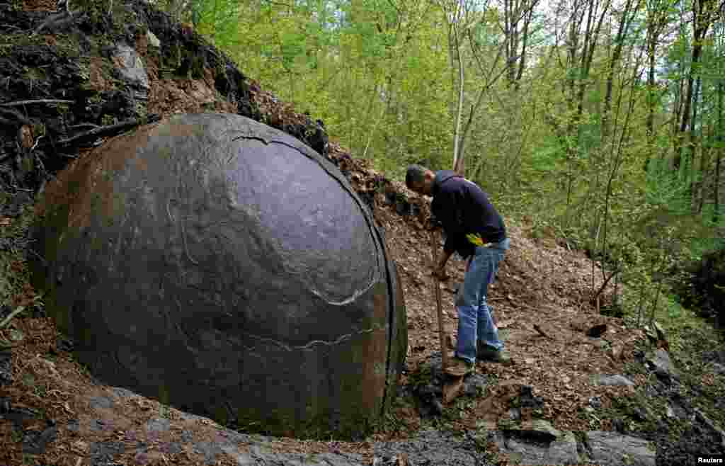Suad Keserovic cleans a stone ball in the village of Podubravlje near Zavidovici, Bosnia-Herzegovina. Keserovic claims that the stone sphere is 3.30 meters in diameter and weighs an estimated 35 tons. Controversial archaeologist Semir Osmanagic asserts that it is the world's largest man-made sphere and may be 1,500 years old, but others cast doubt on this claim. Hundreds of tourists from around the world have visited the stone. (Reuters/Dado Ruvic)