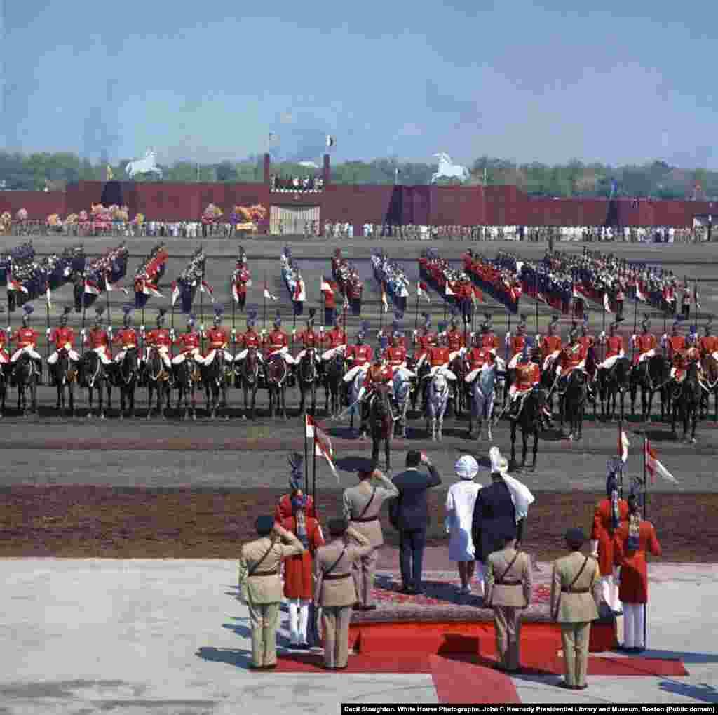 Первая леди, одетая в белое, наблюдает за парадом всадников и гвардейцев в Лахоре в первый день визита в Пакистан.