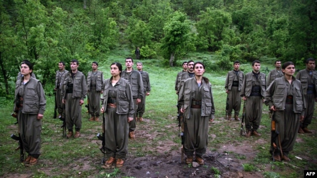 Kurdistan Workers' Party (PKK) members stand at attention after arriving in the northern Iraqi city of Dohuk on May 14.