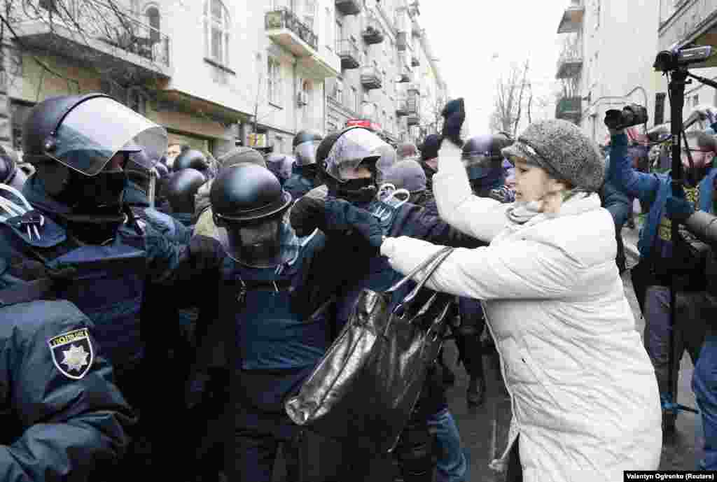A woman attacks police as they attempt to clear the way for a police van holding Saakashvili.