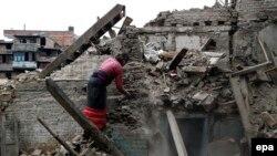 Женщина на руинах развалившегося после землетрясения здания. 15 мая 2015 года.