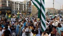 Supporters of the Pakistani Jamaat-e-Islami party carry flags and signs at a rally in support of Kashmir on August 6.