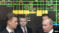 Russian Prime Minister Vladimir Putin (right) speaks with the head of Gazprom, Aleksei Miller (left), at Gazprom headquarters in Moscow on January 13.