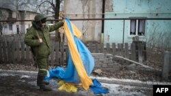 Пророссийский боевик снимает украинский флаг в Углегорске Донецкой области, 7 февраля 2015 года