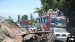 A convoy of local residents travels past the wreckage of a truck as they flee from military operations against Taliban militants in the Naway Kalay area of the Swat Valley.