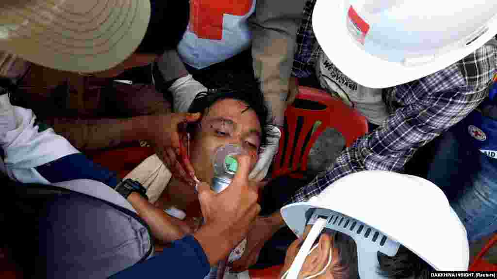 BURMA -- Medics attempt to treat an injured man of his gunshot wounds in Dawei, Myanmar, February 28, 2021, in this still image from video obtained via social media