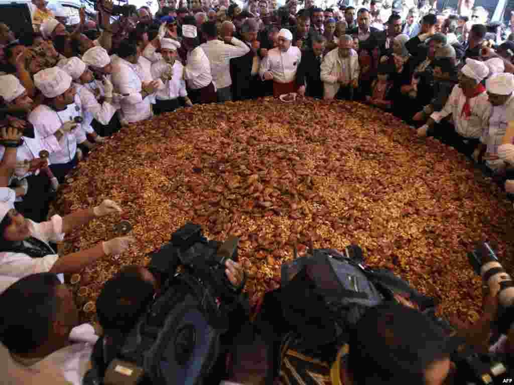 Палестынскія кухары вакол гіганцкага мусахана (кураціна з арэхамі і спэцыямі)