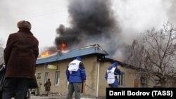 Сотрудники миссии ОБСЕ на месте обстрела одного из жилых районов города Мариуполя. 24 января 2015 года.