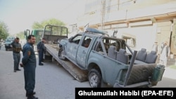 FILE: Afghan police officials inspect a damage vehicle, after it hit a bomb blast, in Jalalabad, the capital of Nangahar Province in April.