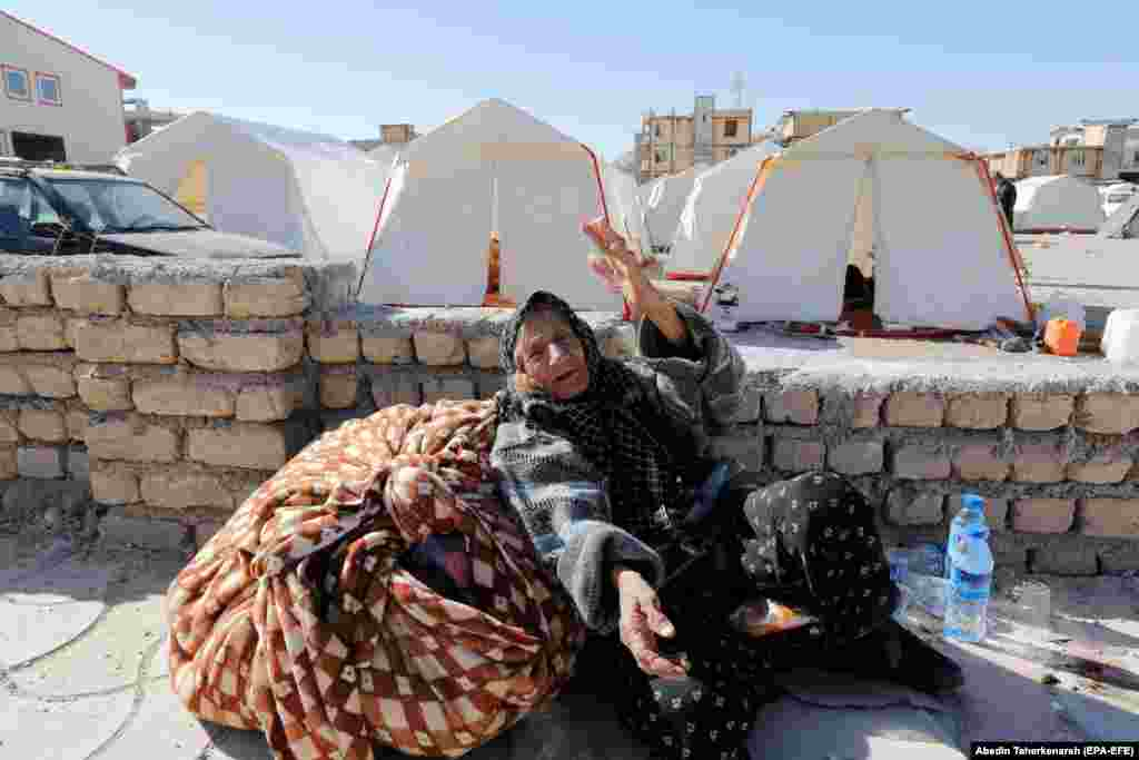 An elderly woman sits near tents erected for victims of the earthquake in the city of Sarpol-e Zahab in Iran's Kermanshah Province on November 14. (epa-EFE/Abedin Taherkenareh)