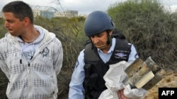 A policeman holds the remains of a rocket launched by Palestinian militants from the Gaza Strip which hit the coastal city of Ashdod on March 24.
