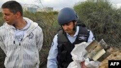 Израильский полицейский с остатками ракеты, выпущенной палестинскими боевиками по городу Ашдод, 24 марта 2011