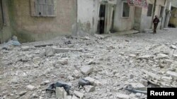 A man walks next to rubble on a street with damaged houses in Baba Amro, near Homs, on February 8.