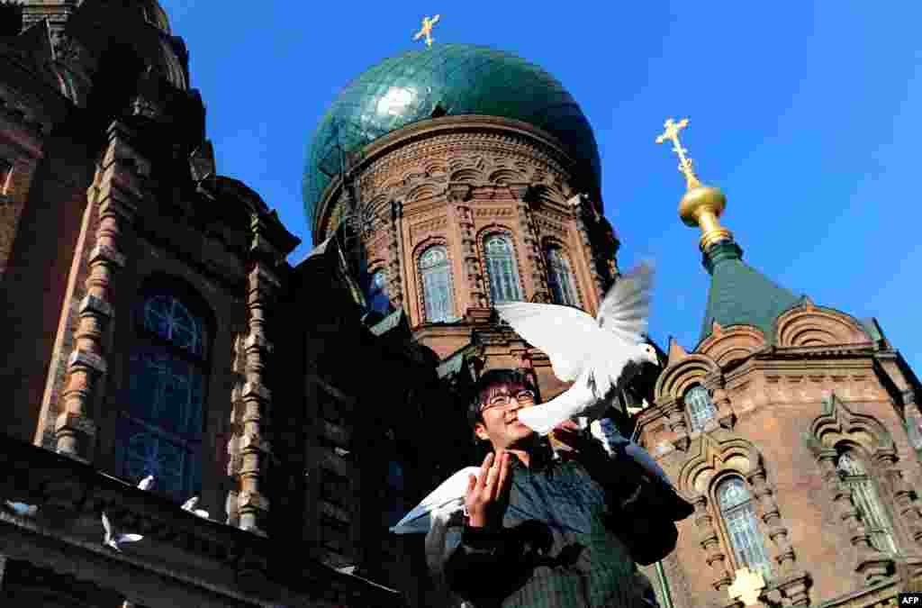 "A man feeds pigeons beneath the onion dome rooftop of St. Sophia Cathedral, a former Russian Orthodox church in Harbin in northeast China. Harbin has opened a ""Russian village"" to attract tourists across the nearby border."