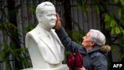 A woman touches the bust at the grave of late Yugoslav President Slobodan Milosevic in the town of Pozarevac, Serbia.