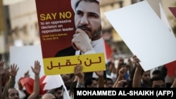 Bahraini protesters hold placard portraying Sheikh Ali Salman during a demonstration against his arrest in June 2015.