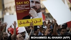 Bahraini protesters hold a placard portraying Sheikh Ali Salman, head of the Shiite opposition movement Al-Wefaq, during a demonstration against his arrest on June 16, 2015, in the village of Jidd Hafs, west of Manama.