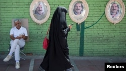 Një grua iraniane përdor telefonin derisa ecën rrugës...