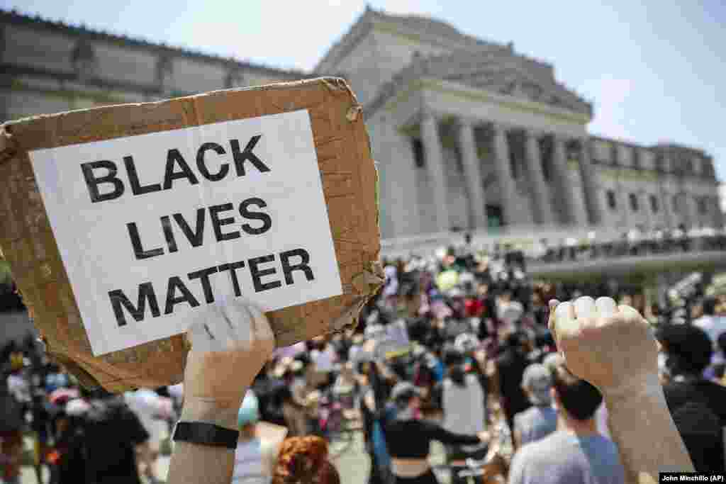 """A protester holds a sign that reads """"BLACK LIVES MATTER"""" during a Juneteenth rally outside the Brooklyn Museum, Friday, June 19, 2020, in the Brooklyn borough of New York."""
