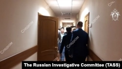 In a press handout from Russia's Investigative Committee, officers carry out an operation to detain Anatoly Kairo.