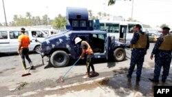 Работники коммунальных служб и сотрудники сил безопасности у места взрыва на въезде в шиитский район Кадимия. Багдад, 24 июля 2016 года.