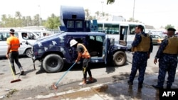 Коммуналдық қызмет өкілдері мен полиция Бағдадтың Кадимия ауданына кіреберісте болған жарылыс орнын тазалап жатыр. Ирак, 24 шілде 2016 жыл.