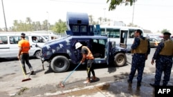 Iraqi workers clean the pavement as security forces stand guard at the site of a deadly suicide bombing near a Shi'ite shrine in Baghdad on July 24.