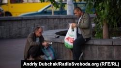 Чоловіки на вокзалі щойно отримали новий довідник із адресами й контактами місць, куди може звернутися бездомна людина