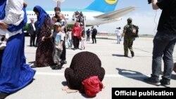 Лежащая на земле женщина на фоне самолета, доставившего узбекистанцев с Ближнего Востока. 30 мая 2019 года.