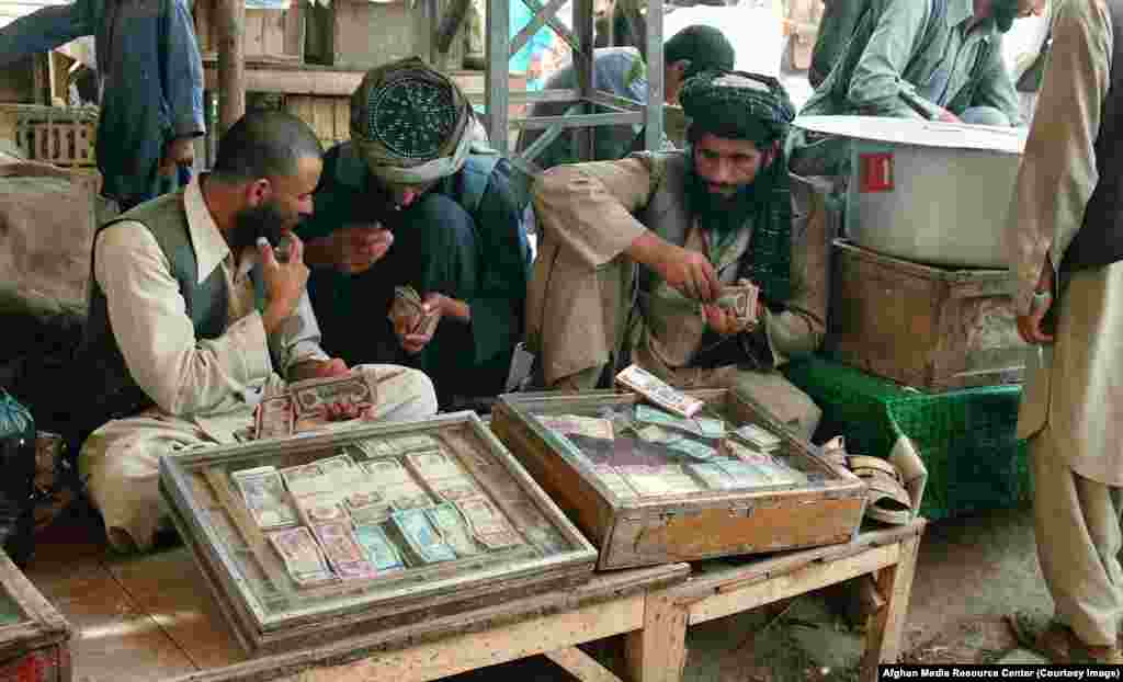 As well as their main task of chronicling the war, the teams of AMRC photographers shot everyday life, like these money changers in Peshawar.