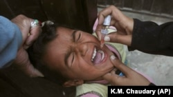 A health worker gives a polio vaccination to a child in Lahore on March 25.