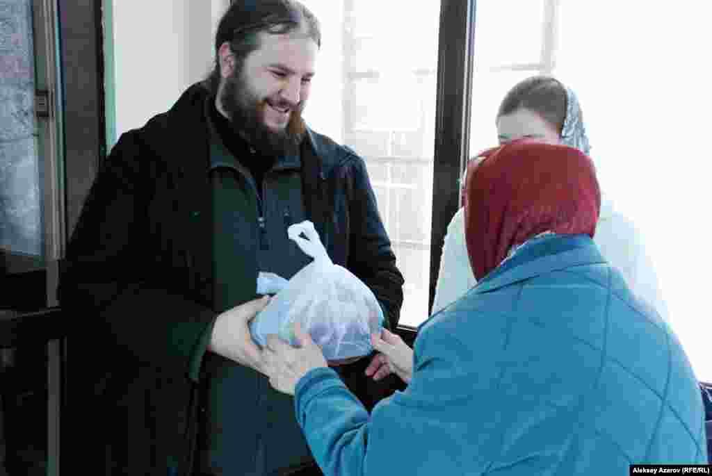 Шіркеуге келушілердің бірі Алматыдағы Никольский соборының священнигі Вячеслав Пугачевқа дәм ұсынып жатыр.