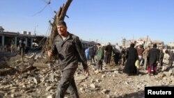 Nje polic i plagosur shihet duke ecur afër vendit të sulmit vetëvrasës në Kirkuk