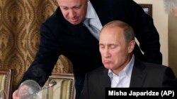 Yevgeny Prigozhin (solda) prezident Putinin xarici alimlərə verdiyi ziyafətdə xidmət göstərərkən