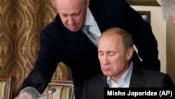 Yevgeny Prigozhin (solda) prezident Vladimir Putinə iaşə xidməti göstərir