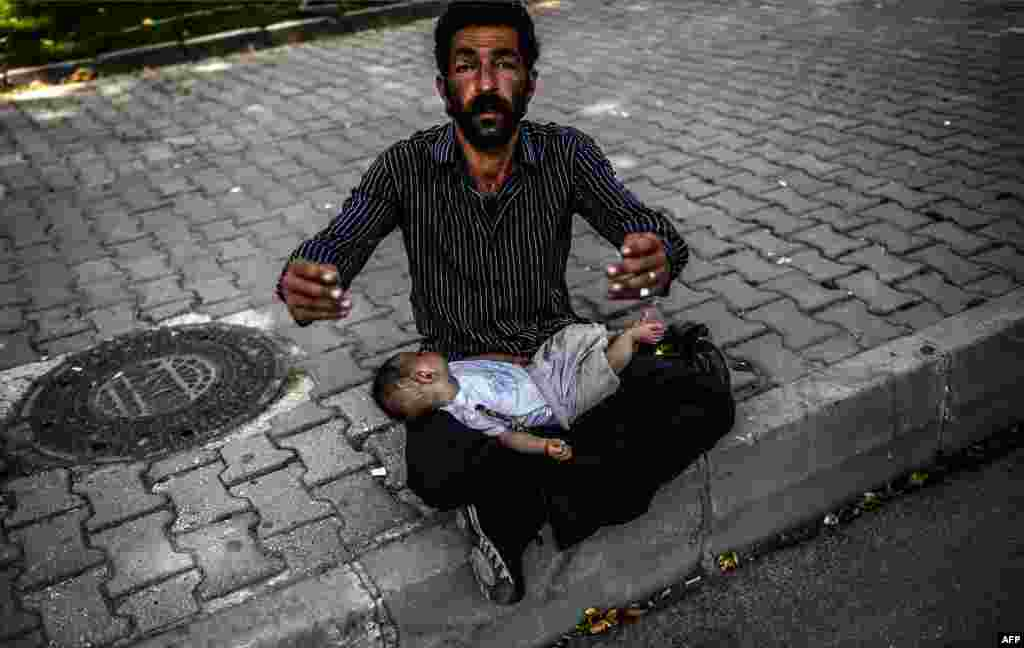 A Syrian refugee man gestures as he begs on the street with a baby lying on his lap in Istanbul on June 19. (AFP/Bulent Kilic)