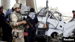 An Iraqi soldier stands guard at the site of a bomb attack in Baghdad's Hussainiya district on May 6.