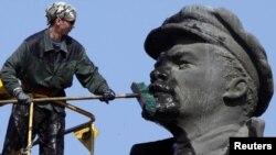 Лениннің ескерткішін жуып жатқан жұмысшы. (Көрнекі сурет)