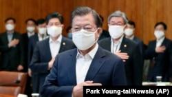 Президент Южной Кореи Мун Чжэ Ин в маске отдает честь национальному флагу на экстренном совещании по экономическим мерам в ответ на вспышку коронавируса в Президентском Голубом доме в Сеуле, 30 марта 2020 г.