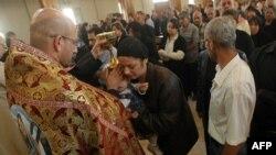 قس يبارك طفلاً في كنيسة ببغداد