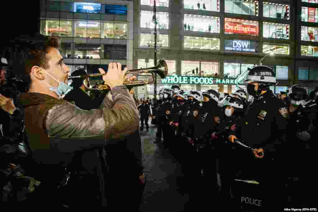 A Black Lives Matter (BLM) demonstrator plays the trumpet facing the police during a protest at Union Square in New York, New York, November 5, 2020.