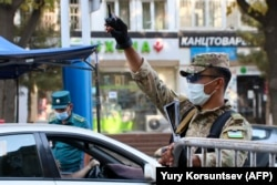 An officer raises his hand as a traffic policeman checks the ID of a driver at a checkpoint amid the ongoing coronavirus disease pandemic in Tashkent on July 23.